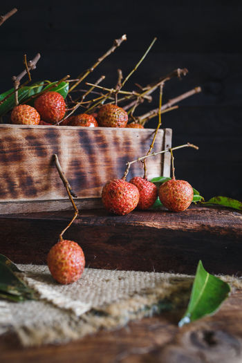 Close Of Lychees By Container On Wooden Table