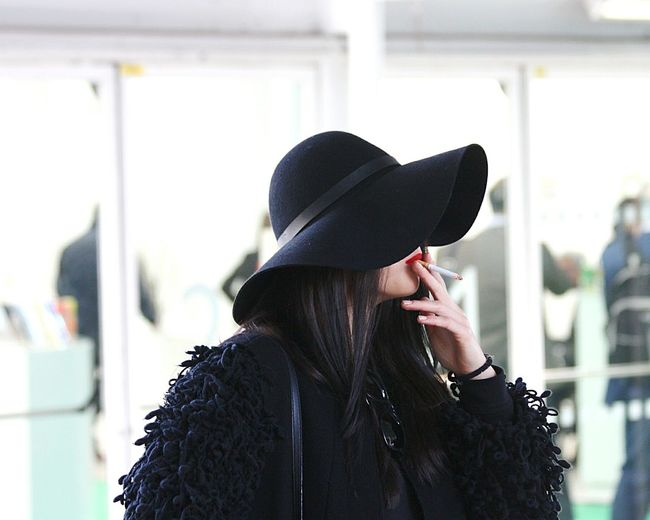 Woman wearing black hat smoking cigarette