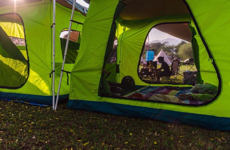 Green Tent With Transparent Patches, Person In Background