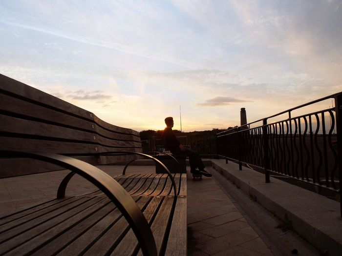 Man Sitting On Bench At Observation Point Against Sky During Sunset