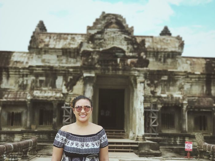 Portrait Of Smiling Woman Standing Against Angkor Wat