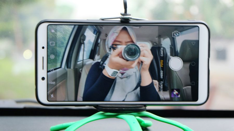 Reflection of woman photographing on camera