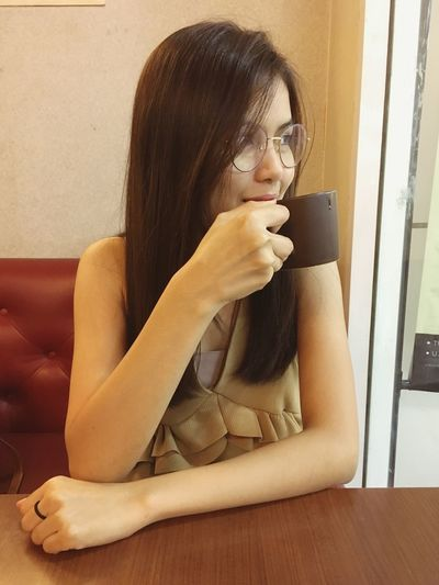 Smiling beautiful woman drinking coffee while sitting in cafe