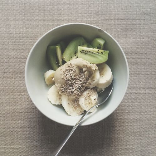 Overhead view of kiwi and banana slices in bowl
