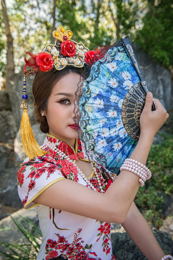 Portrait of young woman wearing qipao holding hand fan