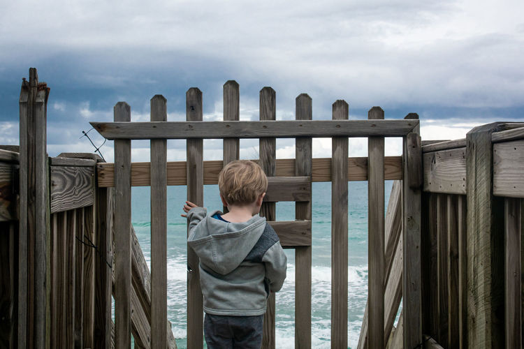 Rear view of boy standing by railing against sky