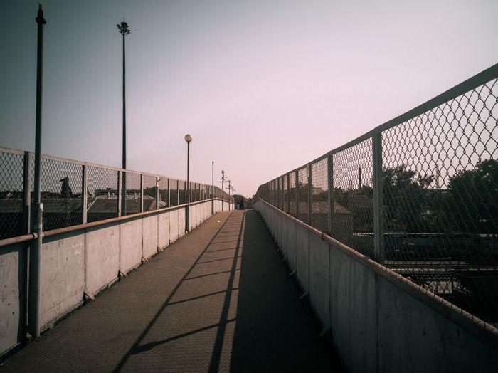 Footbridge over city against sky during sunset