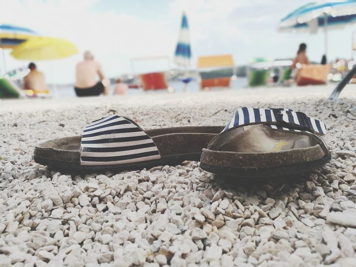 Close-up of slippers on beach against sky