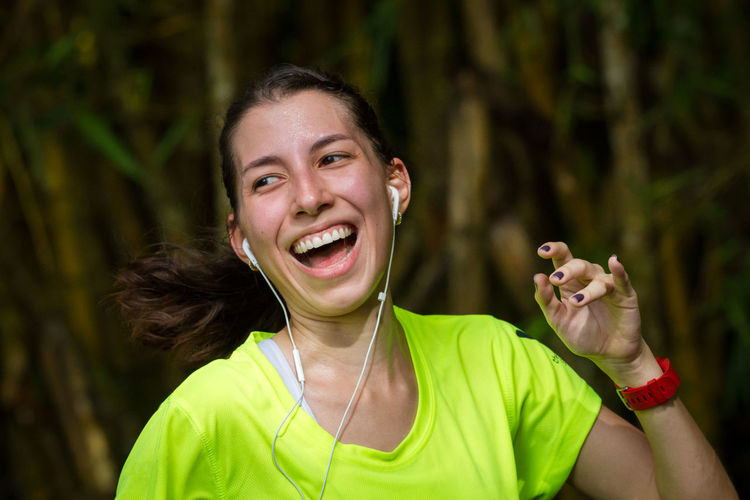 Portrait of smiling young woman with headphones exercising
