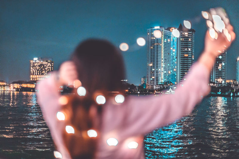 Rear view of man photographing illuminated cityscape against sky