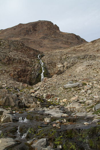 Low angle view of stream flowing through mountain against sky
