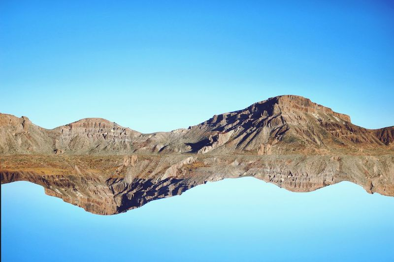 view of mirrored mountains against clear blue sky