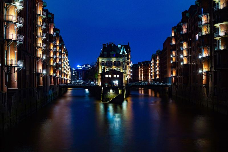 Illuminated canal amidst buildings against sky at night