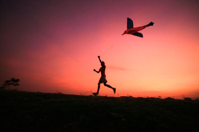 Boy flying kite against sky during sunset