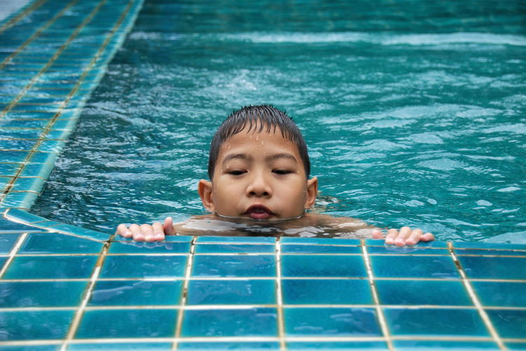 One Person Water Childhood Portrait Swimming Pool Headshot Pool Nature Child Offspring Front View Human Body Part Eyes Closed  Swimming Fun Day Emotion Innocence Floating On Water Contemplation