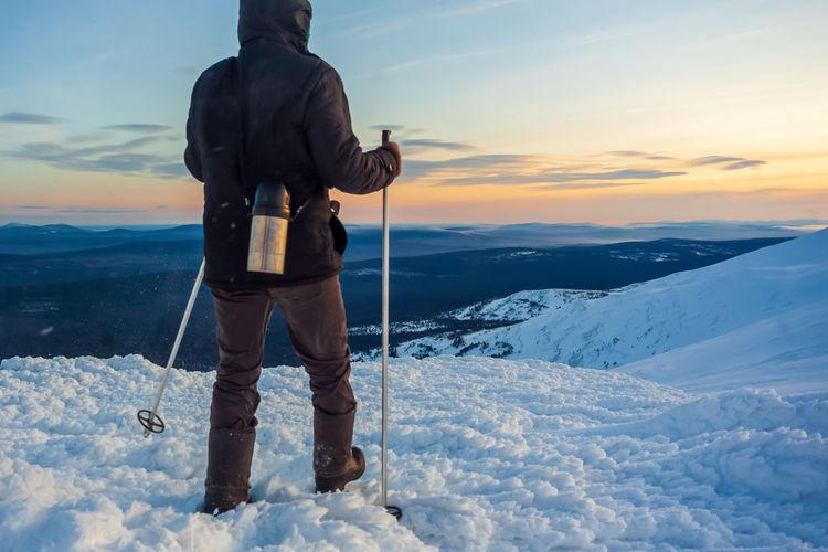 Full length of man standing on snow against sky during sunset