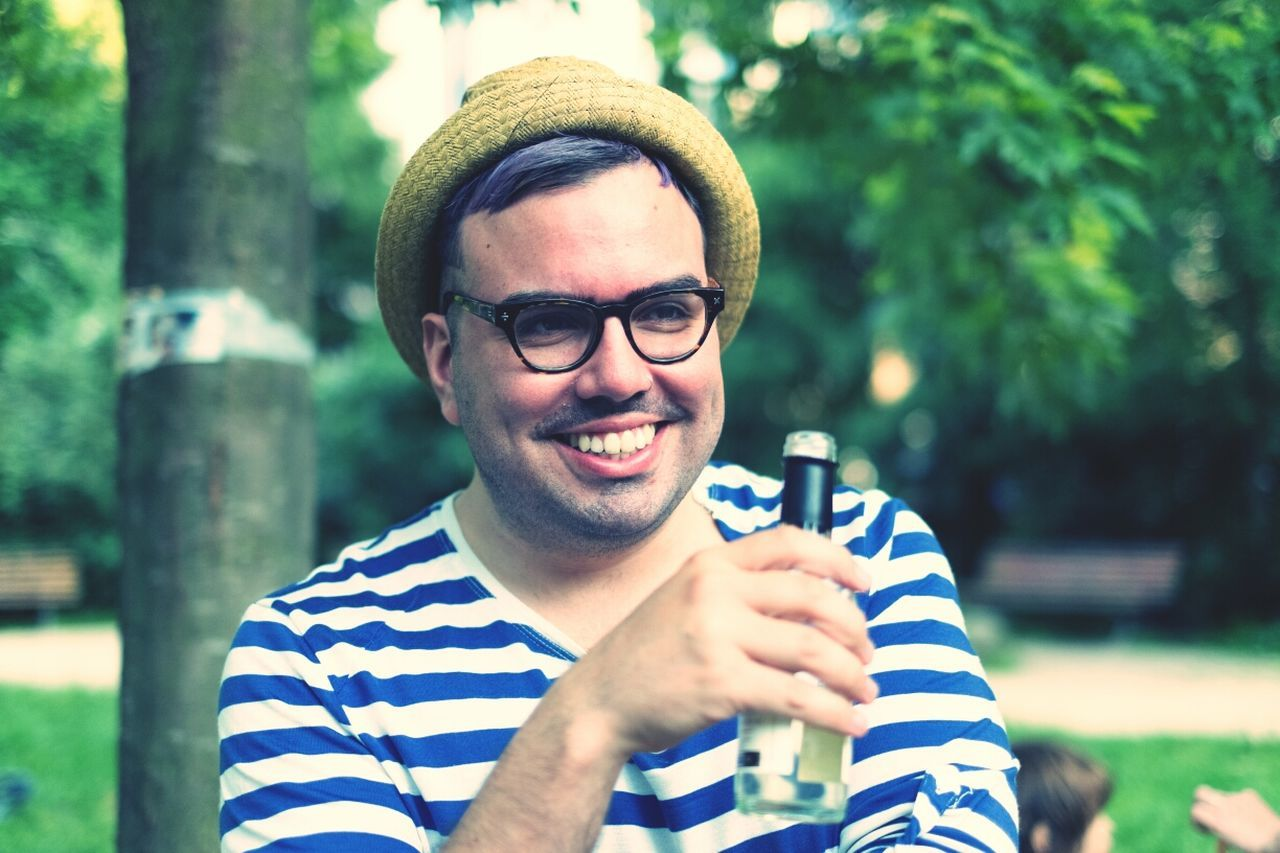 Happy mid adult man holding beer bottle at yard
