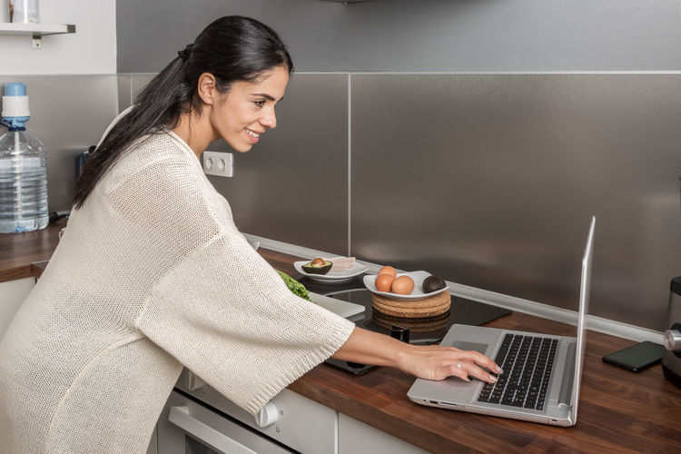 Side view of smiling woman using laptop at kitchen
