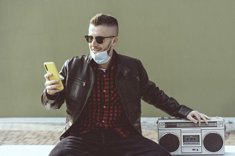 Man wearing sunglasses using smart phone against wall