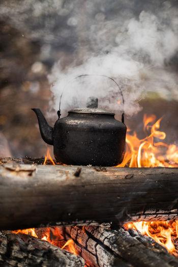 Hot steel kettle on outdoor fire.