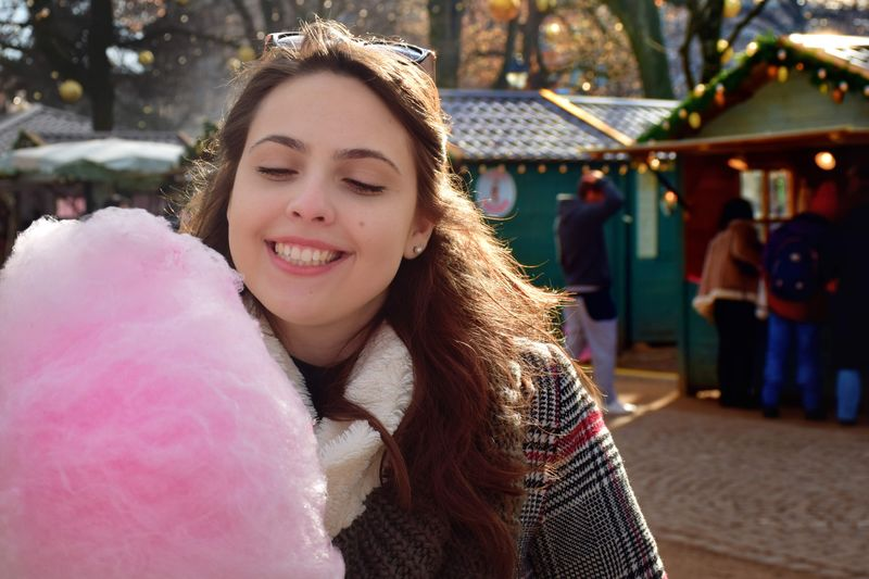 Portrait of smiling young woman eating pink cotton candy