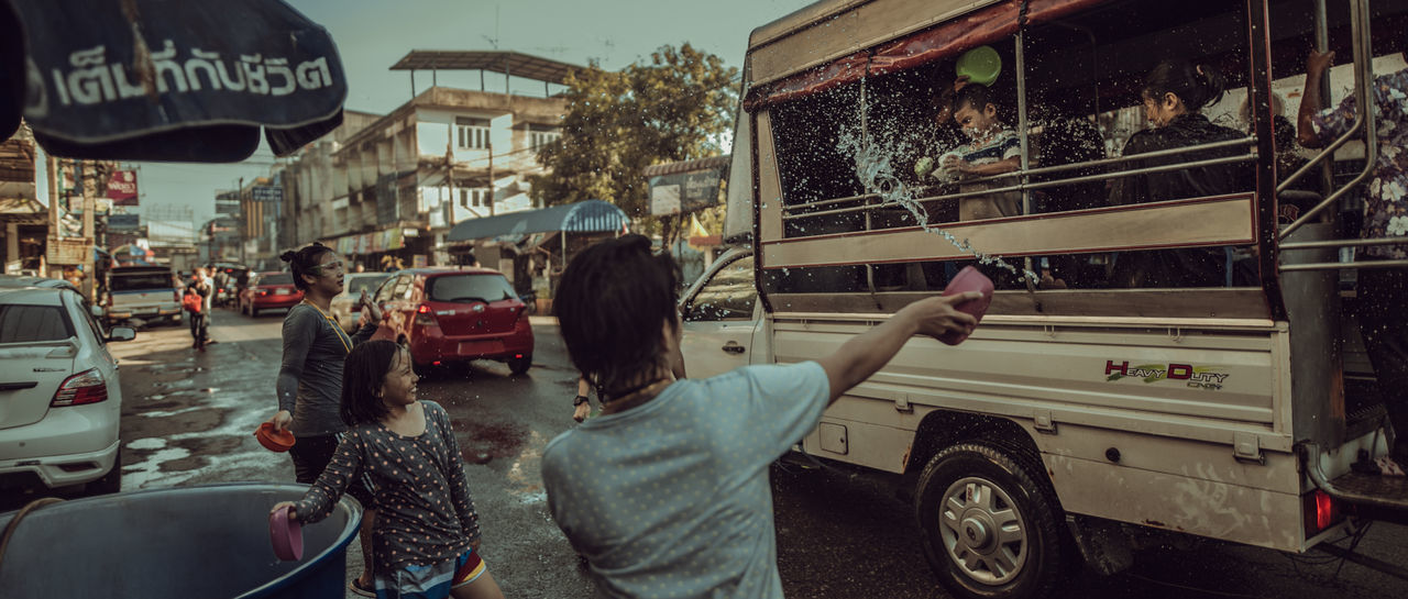 Songkran Festival Thailand Architecture Building Exterior Built Structure Car Child City Land Vehicle Lifestyles Men Mode Of Transportation Motor Vehicle Nature Outdoors Real People Rear View Road Standing Street Transportation Two People Women สงกรานต์