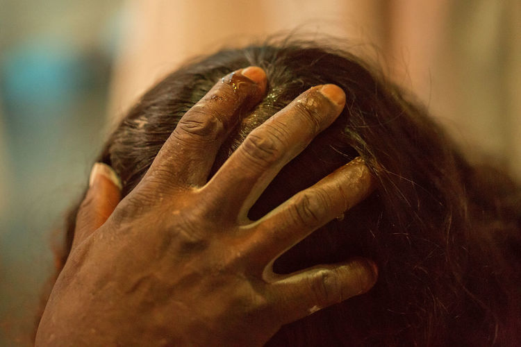 Cropped Hand Of Woman Applying Oil In  Hair