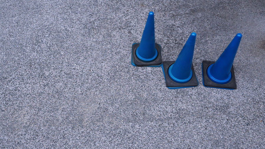Blue traffic cones and old grey textured cement floor. Beach Blue Close-up Day Multi Colored No People Outdoors Sand Sand Pail And Shovel Surface; Caution; Roadwork; Street; Stone; Nobody; Texture; Safety; Sidewalk; White; Construct; Blue; Maintenance; Outdoors; Transportation; Sign; Traffic; Alert; Symbol; Stop; Under; Background; Cone; Work; Danger; Plastic; Construction; Security; Block;