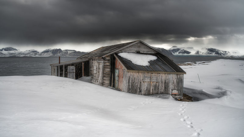 Old wooden building on the edge of thefjord at Ny Alesund Arctic Cold Exterior Fjord Hut Ice Ny Alesund Ocean Old Old Building  Sea Shed Snow Snowcapped Mountain Svalbard  Travel Wood