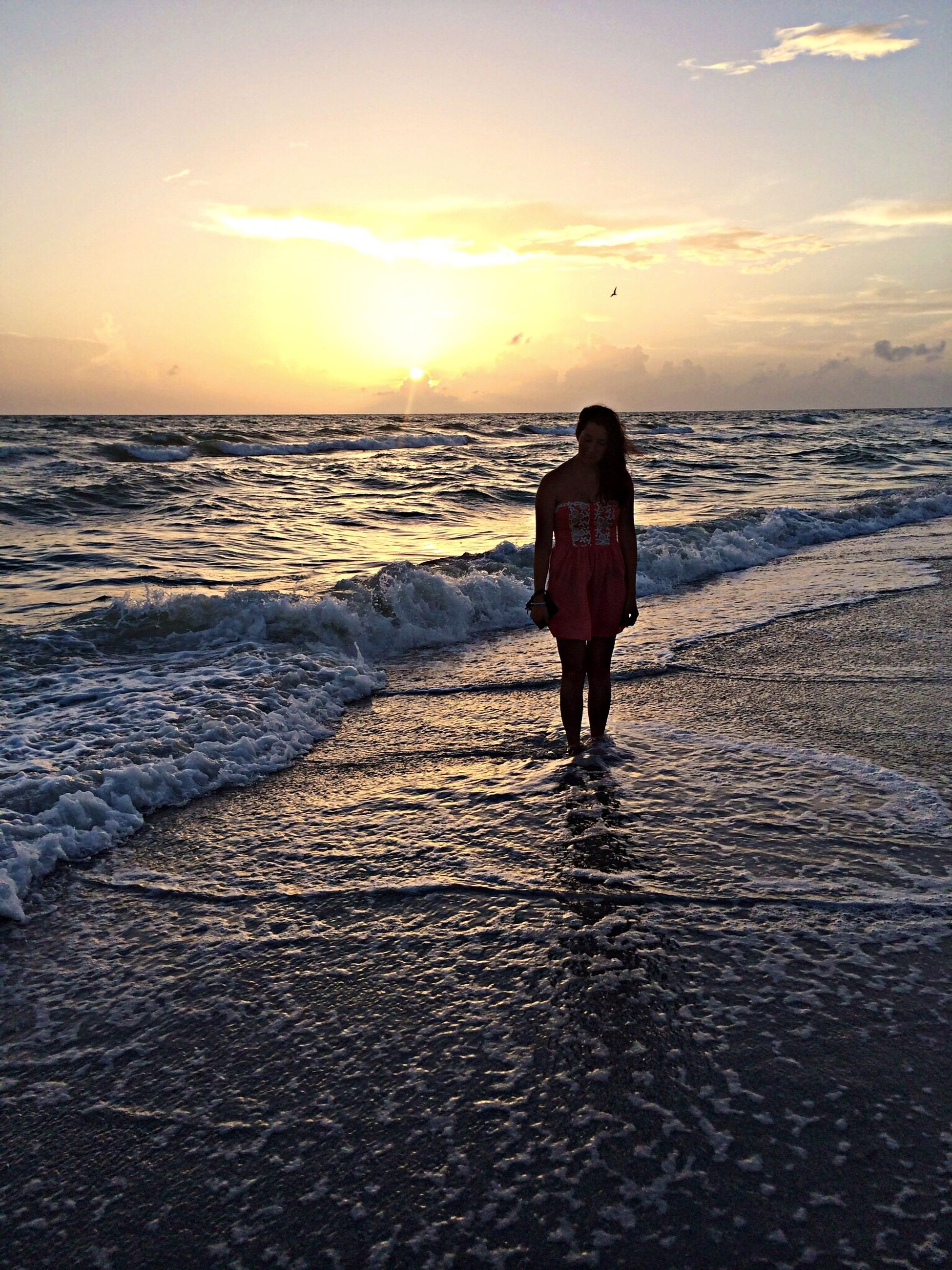 sea, beach, horizon over water, sunset, shore, water, sky, sand, tranquil scene, scenics, tranquility, beauty in nature, lifestyles, leisure activity, standing, rear view, full length, walking