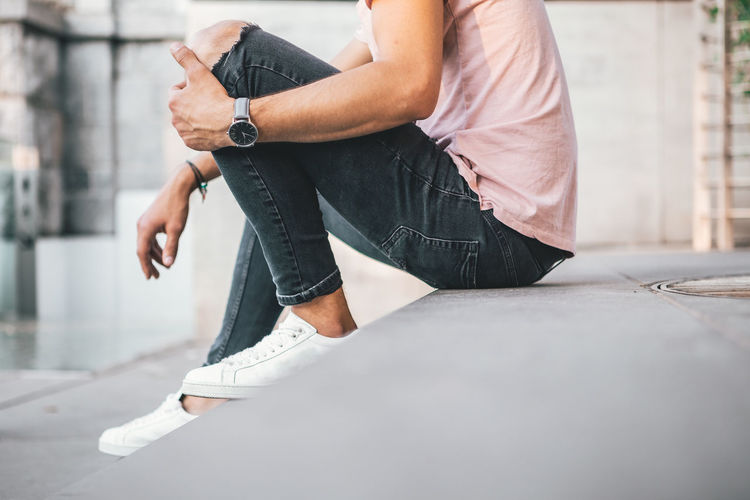 Young Man casually dressed wearing analog watch in the Urban environment One Person Casual Clothing Day Real People Jeans Lifestyles Low Section Architecture City Human Body Part Human Leg Holding Selective Focus Denim Leisure Activity Men Street Midsection Outdoors Waiting Watch Wrist Watch Jewellery Jewelry Young Adult Young Men City City Life Urban