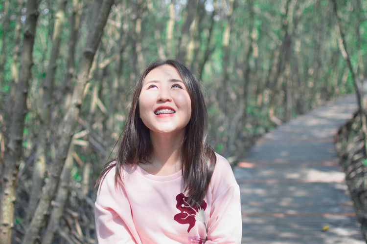 Portrait of smiling young woman standing against trees in forest