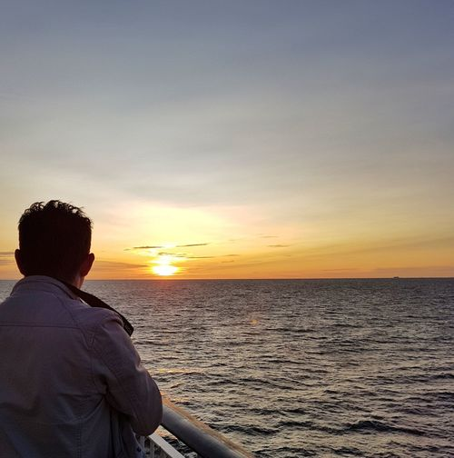 Rear view of mature man by railing against sea during sunset