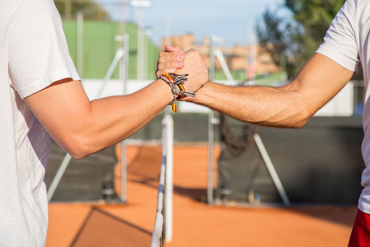 Midsection of sportsmen holding hands at tennis court