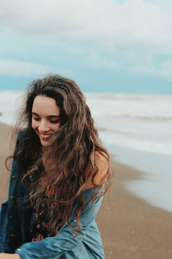 Smiling young woman standing at beach against sky