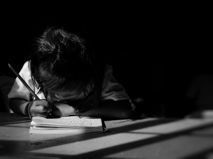 Girl writing homework on table while sitting in darkroom