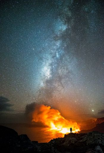 Lava over sea against star field at night