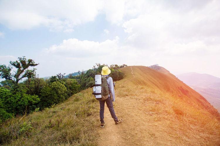 Full length rear view of man standing on landscape against sky