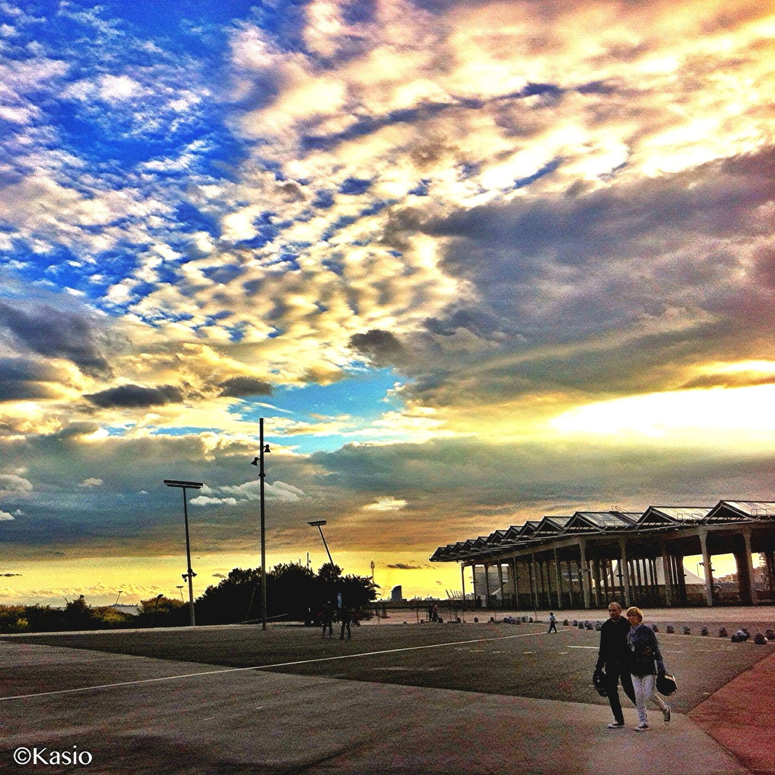 sky, sunset, cloud - sky, men, lifestyles, walking, full length, leisure activity, cloudy, cloud, silhouette, person, built structure, street, road, street light, standing