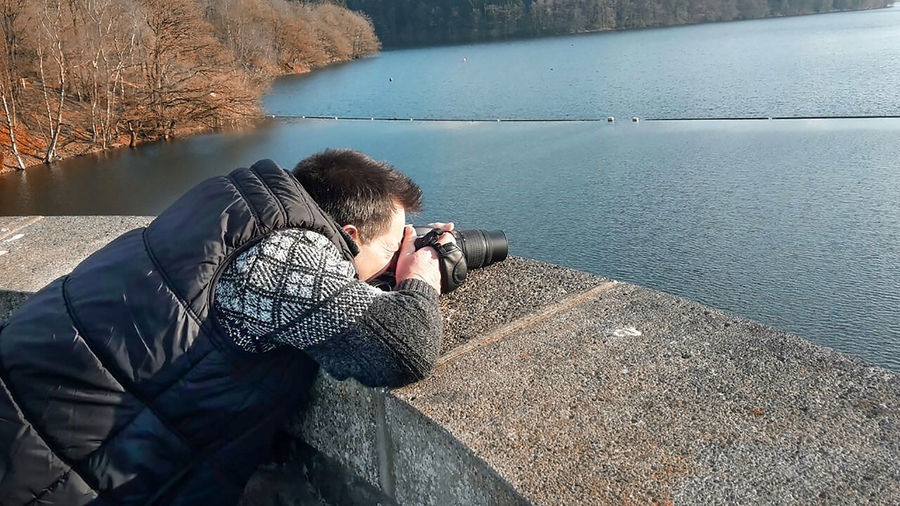 Side View Of Man Photographing On Retaining Wall Against River