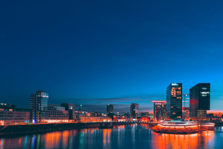Duesseldorf, GERMANY - February 25, 2019: The modern buildings of the new media harbor gloom in the sinking sun light Blue Hour Color Look Blue Media Harbor Medienhafen Düsseldorf 🌾 Best EyeEm Shot Building Exterior Sky Built Structure Architecture Water City Illuminated Nature Copy Space Waterfront Clear Sky Night Reflection Building No People Office Building Exterior River Dusk Outdoors Skyscraper Modern Cityscape