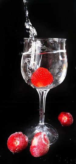 A strawberry in a champagne glass Water Splash Strawberry Champangne Glasses Drink Red Black Background Fruit Cocktail Food And Drink