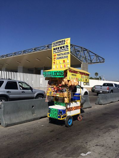 Transportation Land Vehicle Car Mode Of Transport Street Retail  Road Parking Text City Tijuana Immigrant Border Crossing Us Mexico Border Immigration Tijuana, Mexico Political Information Sign Commercial Land Vehicle Signboard Day Blue Commercial Sign