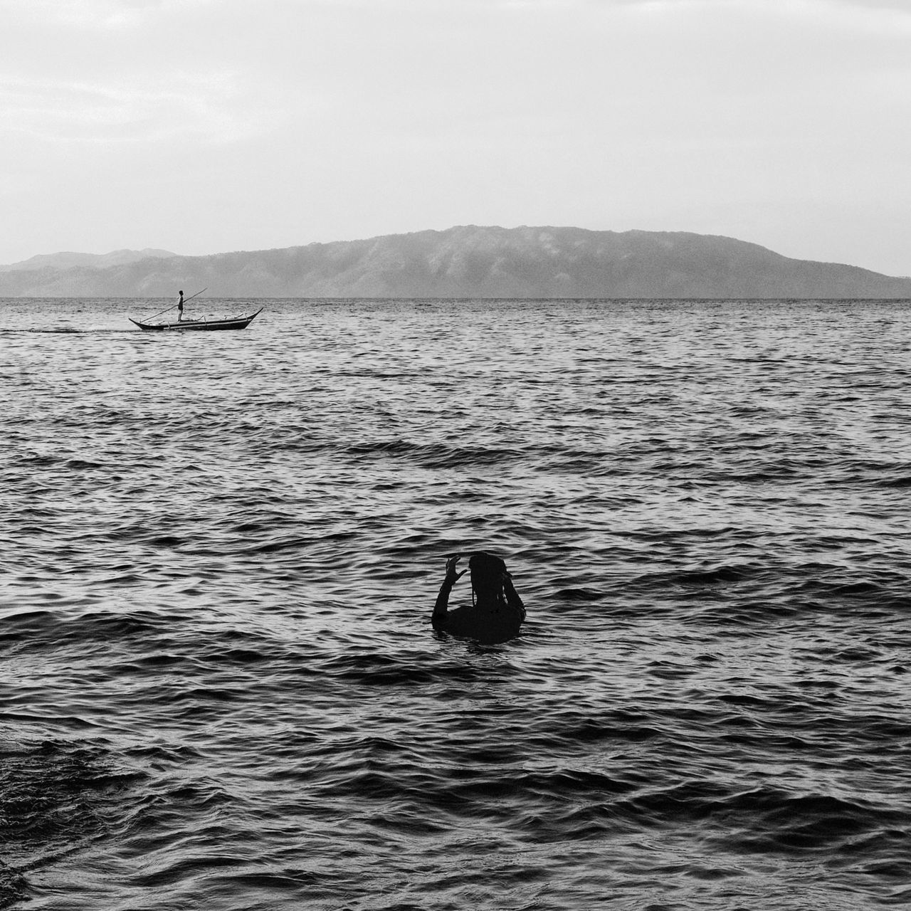 Rear View Of Silhouette Woman Swimming In Sea