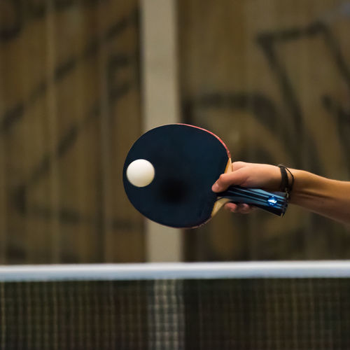 Cropped hand of woman playing table tennis