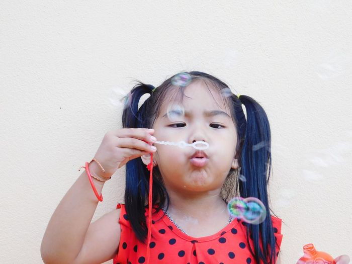 Girl blowing bubbles against wall