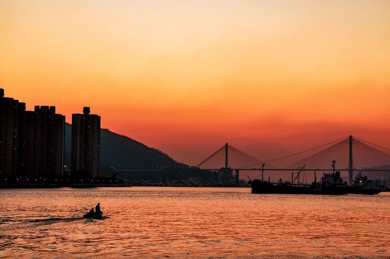 Irange sunset in Hong Kong Sky Sunset Water Architecture Built Structure Nature The Great Outdoors - 2019 EyeEm Awards Orange Color Transportation Silhouette Building Exterior Sea City Waterfront Bridge Bridge - Man Made Structure Connection Clear Sky Travel Destinations Outdoors Cityscape