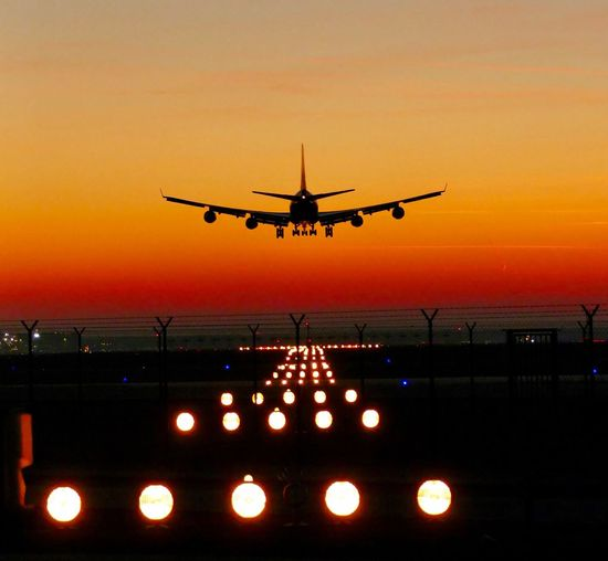 Silhouette airplane landing on runway against sky during sunset