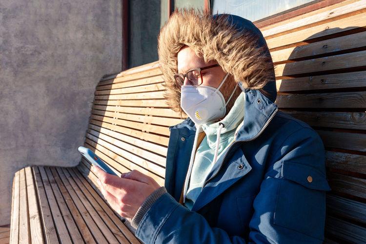 Man wearing mask using smart phone while sitting on bench