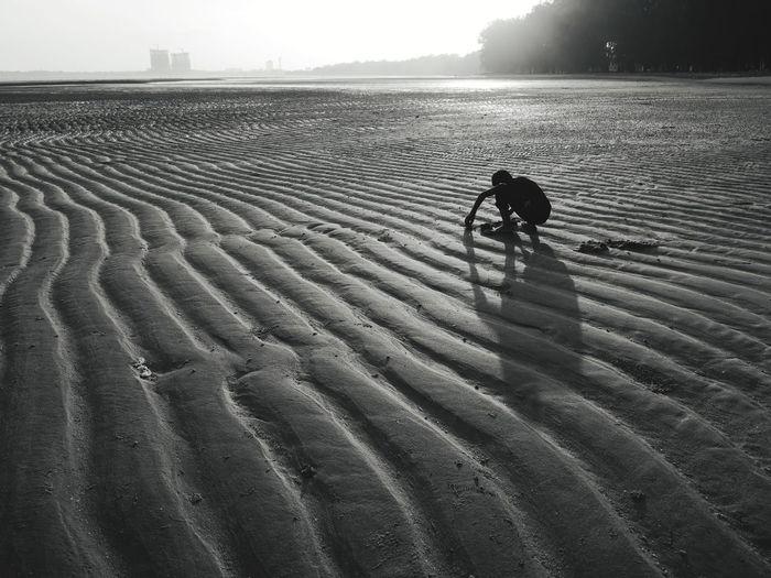 Silhouette man crouching on beach against sky